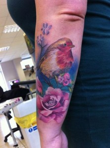 Colorful bird sitting on nest tattoo