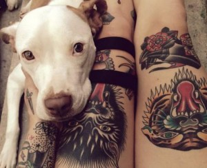 Dog sitting next to tattoo owner