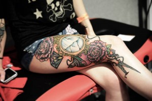 Flower and mirror tattoo on girl thigh