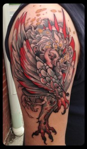 Red demon face with wings and claws tattoo