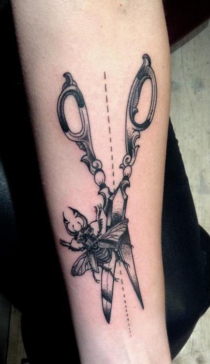 Scissor cutting a bug tattoo